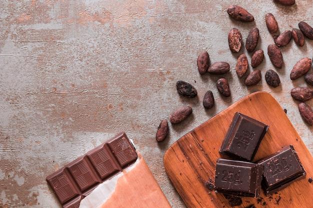 Barretta di cioccolato e pezzi con fave di cacao su fondo rustico Foto Gratuite