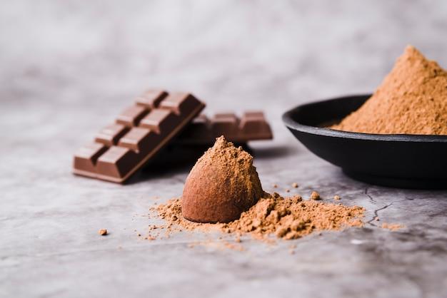 Barretta di cioccolato e polvere di cacao ricoperta di tartufo su fondale in cemento Foto Gratuite