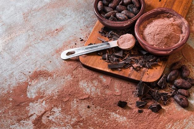 Barretta di cioccolato incrinata con polvere di cacao e fagioli Foto Gratuite