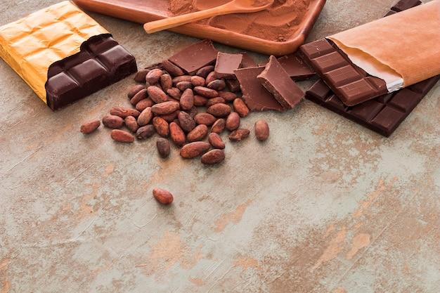 Barrette di cioccolato, fave di cacao e polvere su sfondo grunge Foto Gratuite