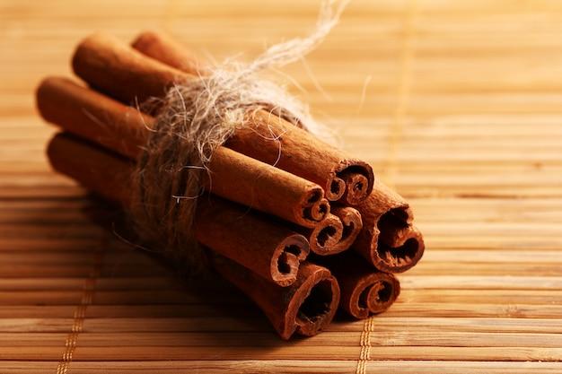 Bastoncini di cannella sul tappeto di legno Foto Gratuite