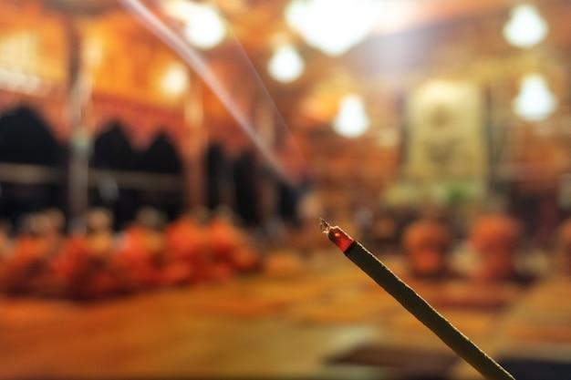 Bastoncini di incenso in fiamme con fumo, bastoncini d'incenso che bruciano in un tempio buddista vintage Foto Premium