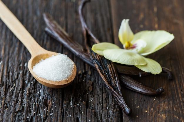 Bastoncini di vaniglia secchi, zucchero e orchidea di vaniglia sulla tavola di legno. avvicinamento. Foto Premium