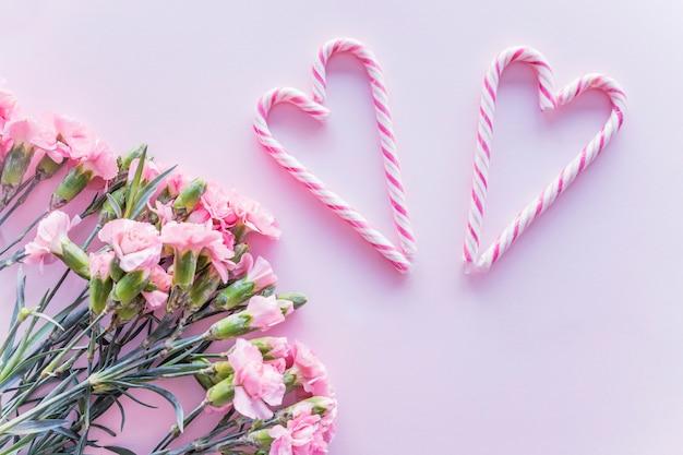 Bastoncini di zucchero a forma di cuore con fiori Foto Gratuite