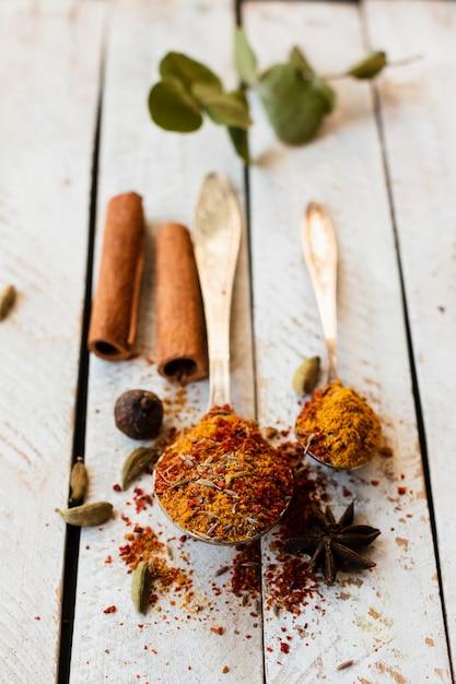 Bastoncini e cucchiaio di cannella con le spezie indiane Foto Gratuite