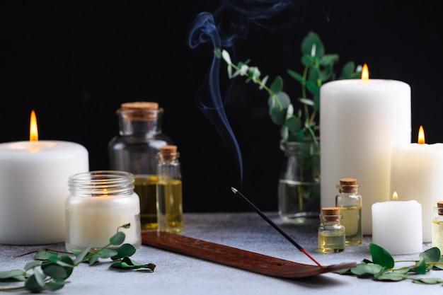 Bastoncino di incenso con fumo su pietra con candele bianche e olii essenziali Foto Premium