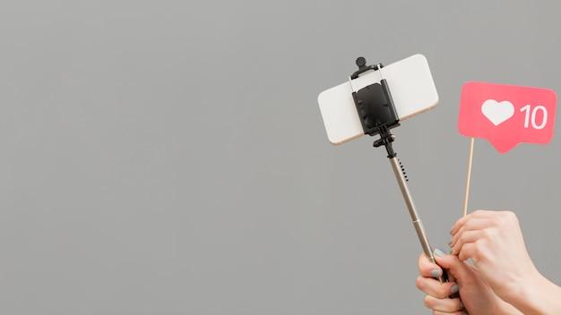 Bastone del selfie della tenuta del blogger del primo piano con il telefono cellulare Foto Gratuite
