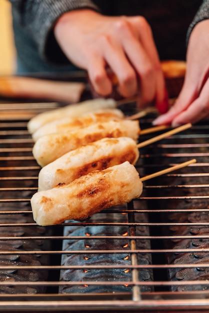 Bastone di formaggio alla griglia sulla stufa a gas griller, cibo di strada a ximending a taiwan, taipei. Foto Premium