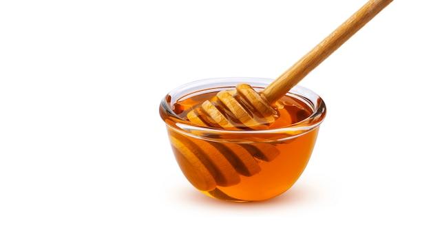 Bastone e ciotola di miele di miele isolati su bianco con il percorso di ritaglio Foto Premium