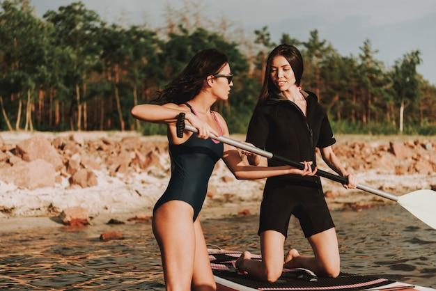 Beautiful females in wetsuit rowing surf con pagaia. Foto Premium