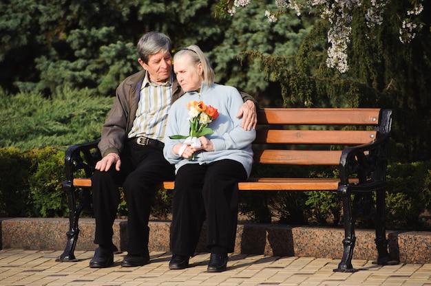 Bei anziani felici che si siedono nel parco di autunno Foto Premium