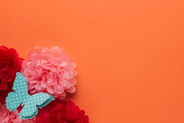 Bei fiori di carta di origami e polka punteggiato farfalla blu su sfondo arancione Foto Gratuite