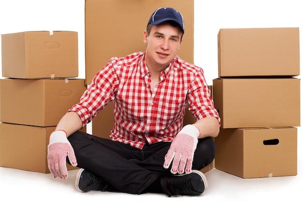 Bel giovane corriere con scatole marroni Foto Gratuite