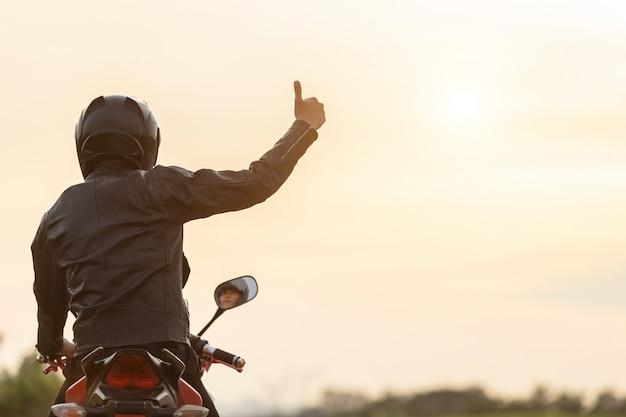 Bel motociclista indossare giacca di pelle, tenendo il casco sulla strada Foto Premium