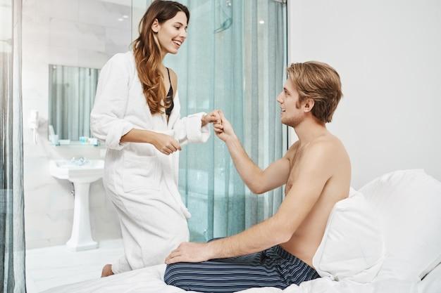 Bel ragazzo con petto nudo seduto sul letto e invitante fidanzata per unirsi a lui. gli amanti felici si sono appena svegliati e si preparano ad andare in spiaggia mentre sono in vacanza in egitto. Foto Gratuite