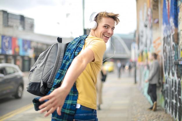 Bel ragazzo in esecuzione in strada durante l'ascolto di musica con le cuffie Foto Premium