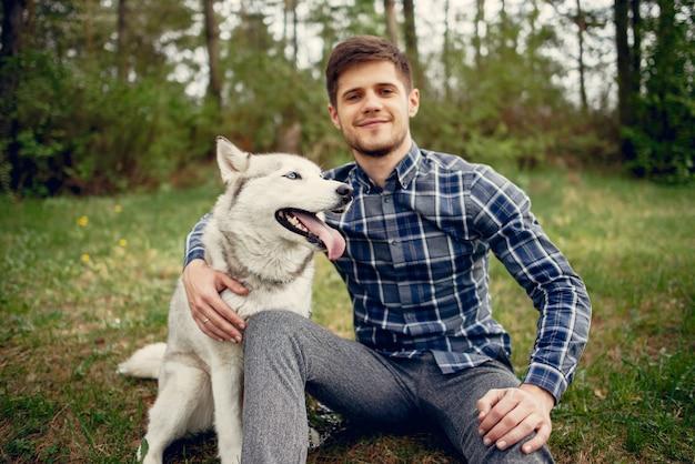 Bel ragazzo in un parco estivo con un cane Foto Gratuite