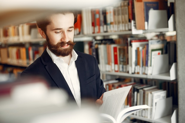 Bel ragazzo studia presso la biblioteca Foto Gratuite