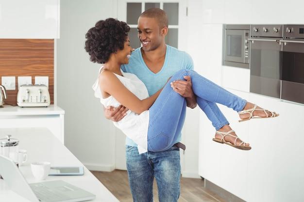 Bell'uomo che trasportano la sua fidanzata in cucina Foto Premium