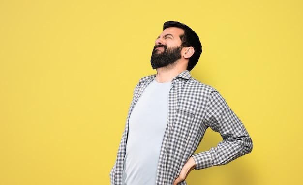 Bell'uomo con la barba che soffre di mal di schiena per aver fatto uno sforzo Foto Premium