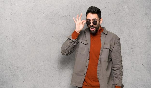 Bell'uomo con la barba con gli occhiali e sorpreso oltre il muro testurizzato Foto Premium