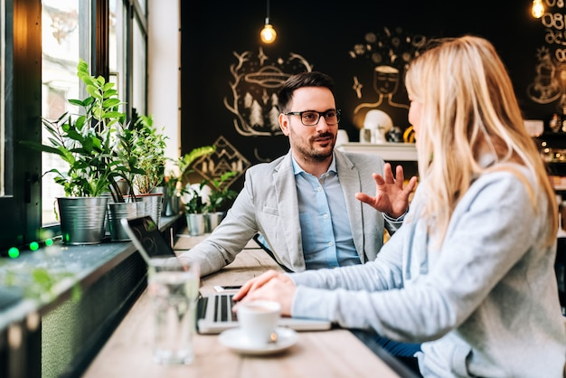 Bell'uomo parlando con una giovane donna bionda al caffè. Foto Premium