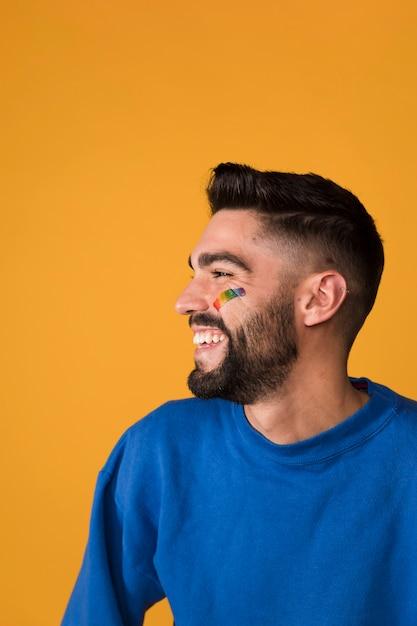 Bell'uomo ridente con arcobaleno lgbt sul viso Foto Gratuite