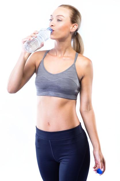 Bella acqua potabile giovane donna dopo aver fatto esercizio su sfondo bianco. Foto Gratuite
