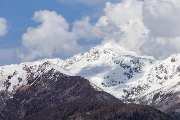 Bella alba nuvolosa nelle montagne con la cresta della neve Foto Premium