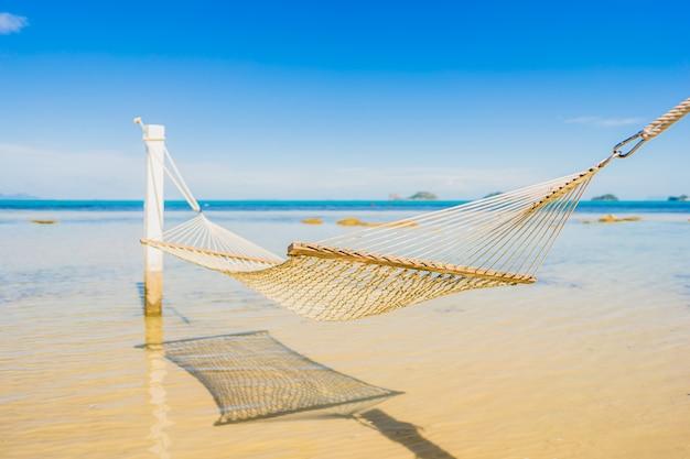 Bella amaca vuota intorno all'oceano tropicale del mare della spiaggia per la vacanza Foto Gratuite