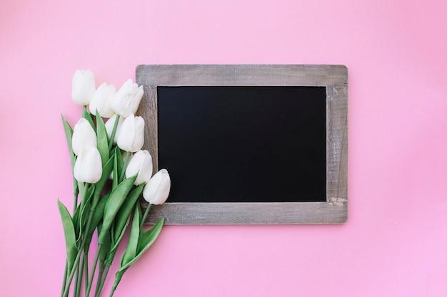 Bella ardesia per mock up con graziosi tulipani su sfondo rosa Foto Gratuite
