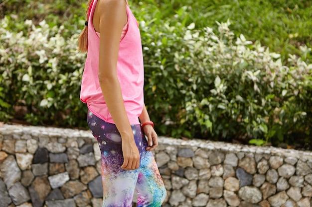 Bella atleta abbronzata donna che indossa leggings con stampa spaziale e canotta rosa che cammina lungo la strada nel parco urbano, riprendendo fiato dopo l'esercizio cardio attivo, preparandosi per la maratona Foto Gratuite