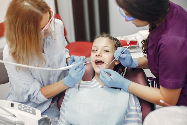 Bella bambina che si siede nell'ufficio del dentista Foto Gratuite