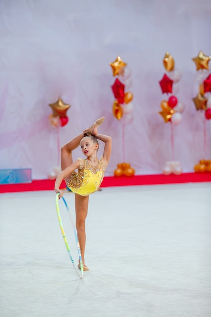Bella bambina ginnasta attiva con le sue prestazioni sul tappeto Foto Premium