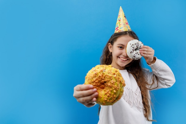 Bella bambina in protezione di compleanno che tiene due ciambella e che posa sul blu Foto Premium