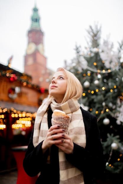 Bella bionda con la torta allo spiedo al mercatino di natale a wroclaw, polonia Foto Premium