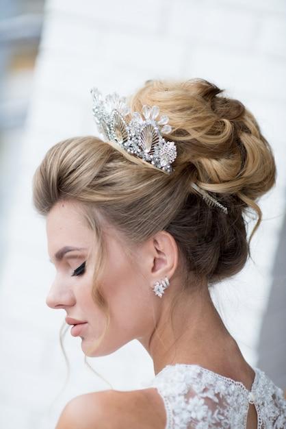 Bella bionda sposa con alta chioma di capelli e preziosa corona d'argento sui capelli Foto Gratuite