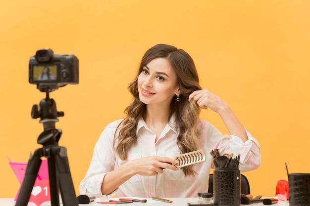 Bella blogger che spazzola i capelli sulla macchina fotografica Foto Gratuite