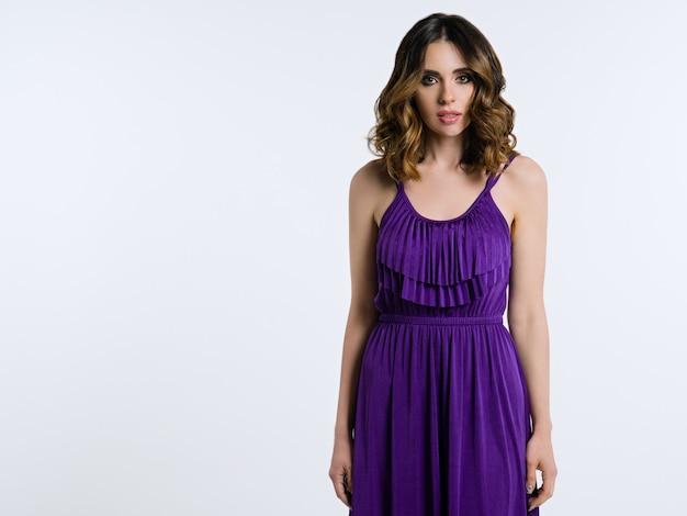 Bella bruna in abito viola su sfondo chiaro Foto Premium
