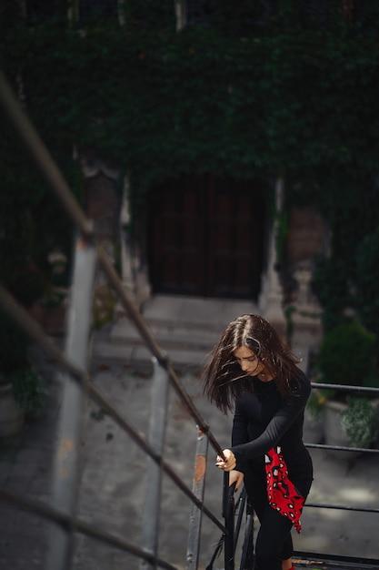 Bella bruna in posa su una scala nera Foto Gratuite