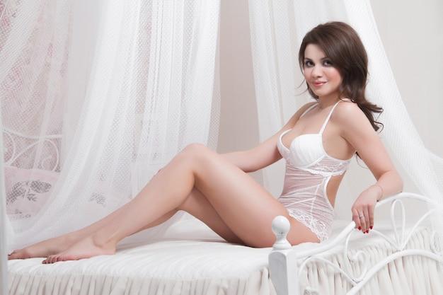 Bella bruna sexy con grandi seni è seduta sul letto. donna sexy nuda in camera da letto. ritratto sexy di castana nudo nell'interno domestico. corpo nudo perfetto signora sexy Foto Premium