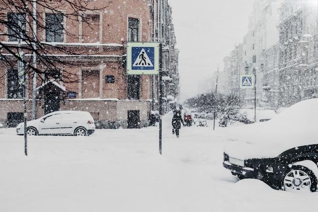 Bella città innevata con mezzi di trasporto e persone, coperta di neve bianca spessa durante la bufera di neve Foto Premium