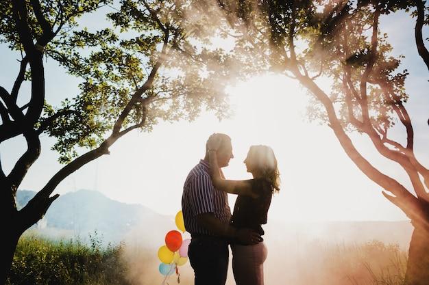 Bella coppia adulta con palloncini colorati si trova sotto un albero Foto Gratuite