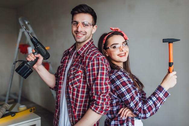 Bella coppia che fa la riparazione a casa, indossando abiti protettivi ben equipaggiati con facce e vestiti disordinati riparazioni a casa Foto Premium