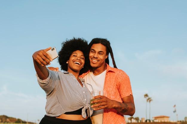 Bella coppia prendendo un selfie in spiaggia Foto Premium