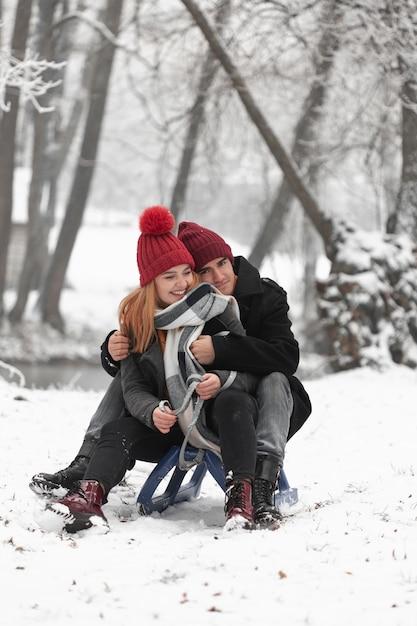 Bella coppia seduta sulla slitta Foto Gratuite