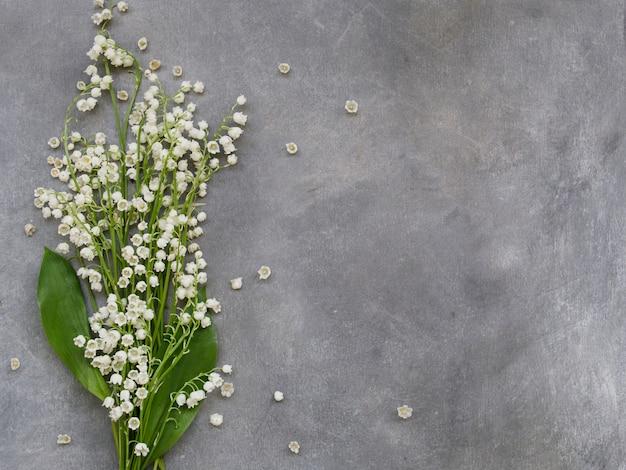 Bella cornice floreale con fiori di gigli della valle su uno sfondo grigio scuro Foto Premium