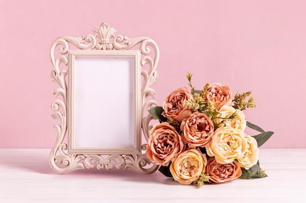 Bella cornice vuota con bouquet di rose Foto Gratuite