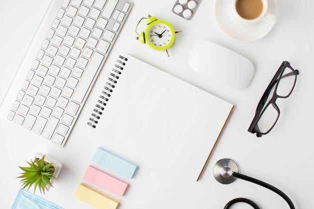 Bella disposizione della scrivania clinica con tazza di caffè e sveglia Foto Gratuite