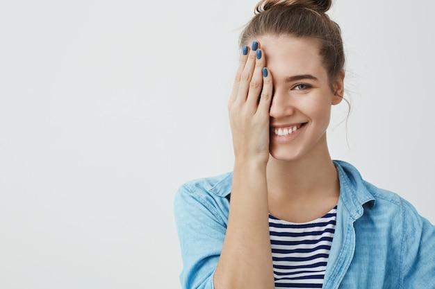 Bella donna adolescente che copre un occhio con la sua mano Foto Gratuite